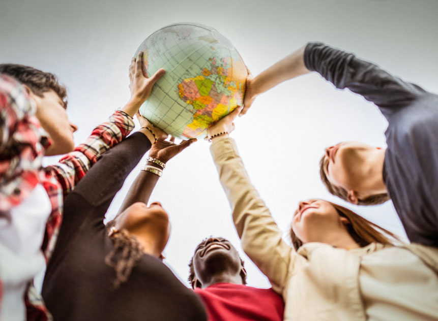 A group of young people standing in a half circle, hold up a globe together with their stretched arms.