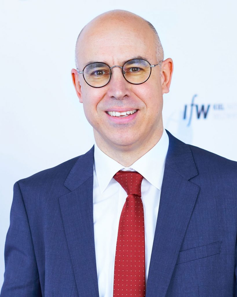 Portrait of bald middle aged man, wearing a suit and glasses, looking into the camera.