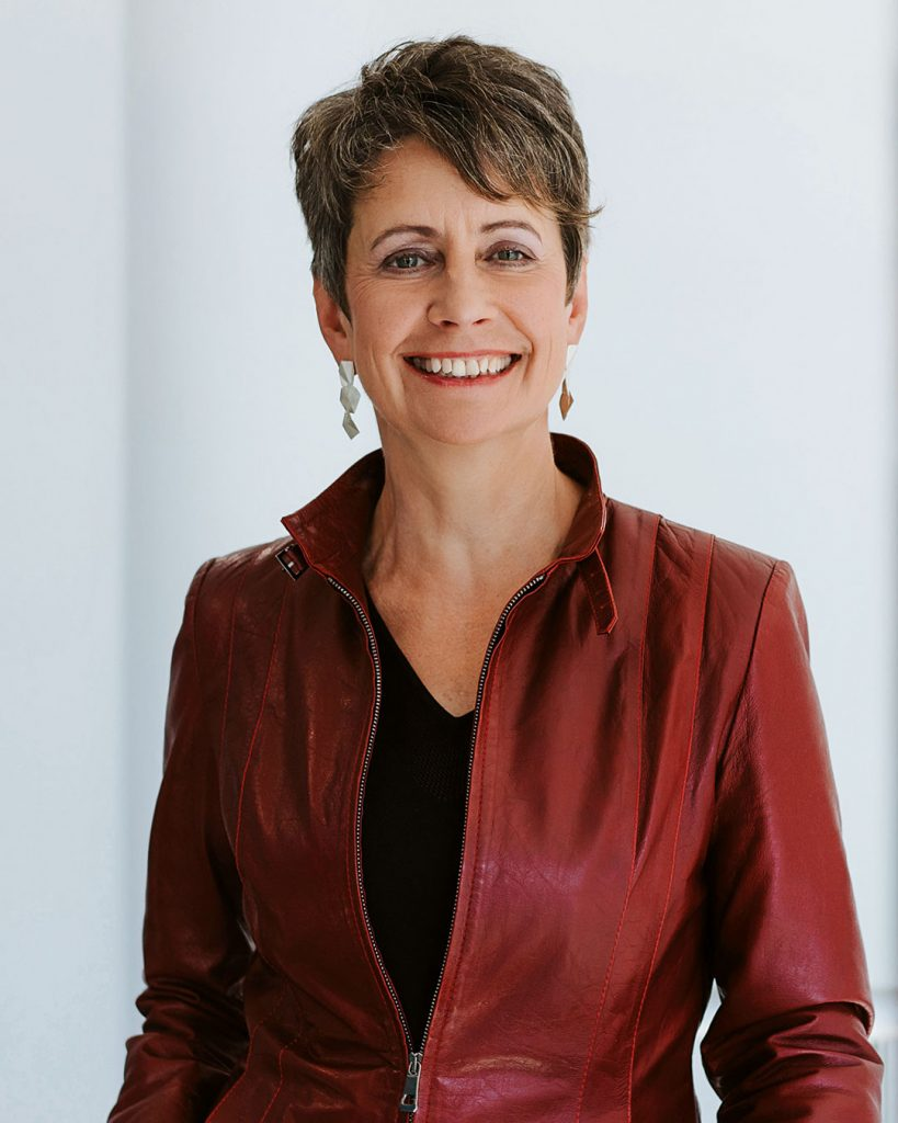 Portrait of a woman with short brown hair, wears an elegant black blouse while smiling in to the camera.