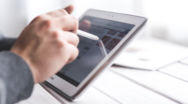 Male hands holding a tablet, browsing the web and manipulating the display with a pen in a professional environment.